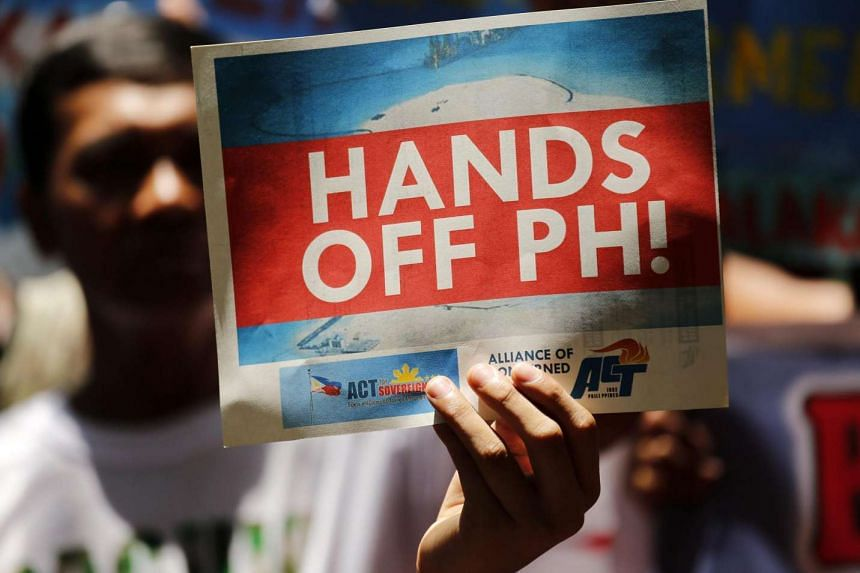 A Filipino protestor holds a placard reading 'Hands Off PH!' as they protest against China's territorial claims over the South China Sea.
