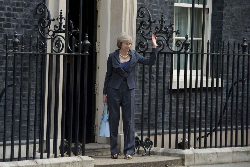 Mrs Theresa May waves to the media from the front door of 10 Downing Street in London on July 12, 2016.