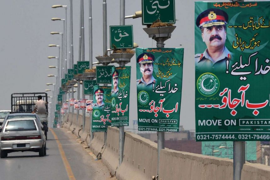 Pakistani commuters drive past posters of army chief General Raheel Sharif in Peshawar.