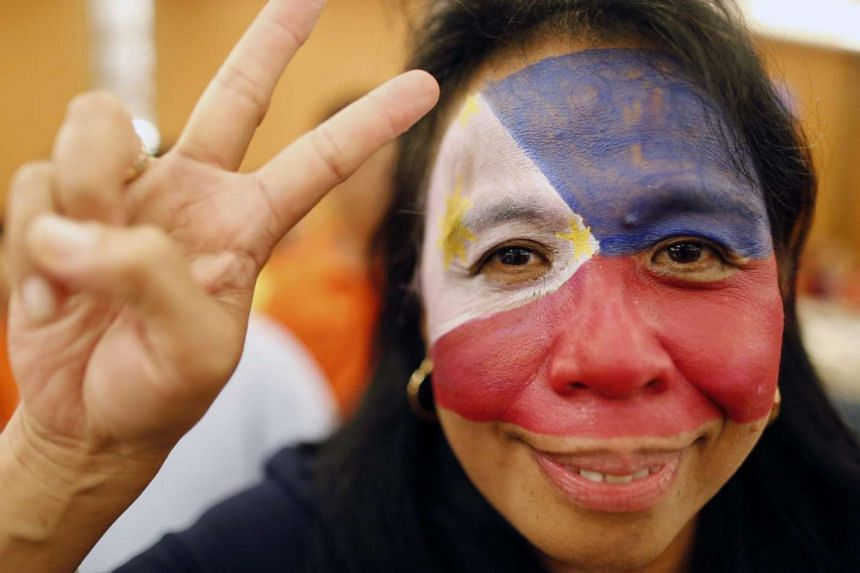 A Filipino activist gestures a victory sign during a celebration on the ruling on the disputed South China Sea in Manila.