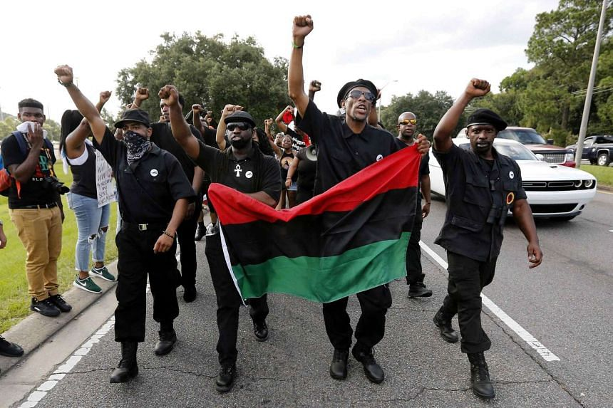 Demonstrators wearing the insignia of the New Black Panthers Party protest the shooting death of Alton Sterling near the headquarters of the Baton Rouge Police Department in Louisiana, US on July 9, 2016.