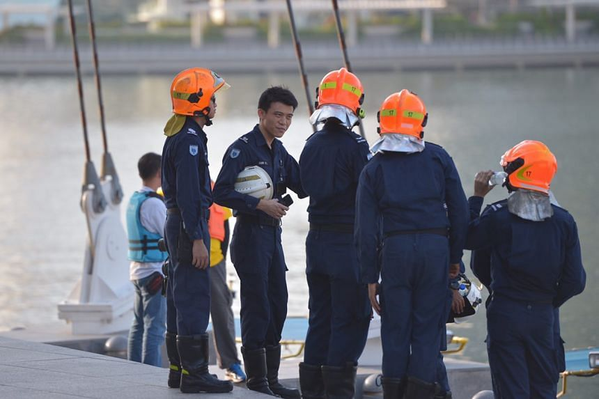 SCDF officers on the site next to the charred bumboat.