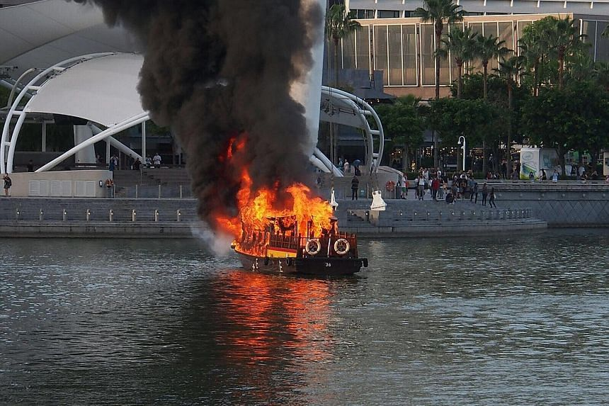 Massive plumes of smoke rising from the burning boat yesterday evening as people gathered on the walkway near the Esplanade. SCDF personnel (right) put out the fire using two water jets from the riverbank.