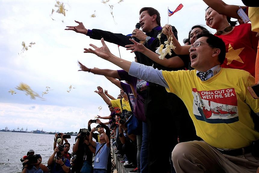 Protesters hurling flowers while chanting anti-Chinese slogans during a rally in Manila over the South China Sea row yesterday.
