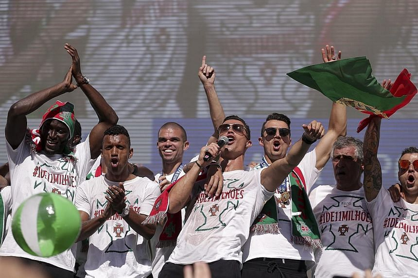 Cristiano Ronaldo (with microphone), his Portugal team-mates and coach Fernando Santos (right) leading celebrations in Lisbon. The Real Madrid forward, who was hauled off during the Euro 2016 final due to injury, may not recover in time for his club'