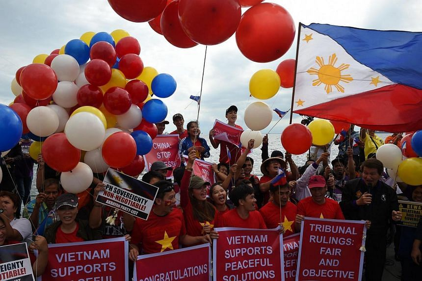 Filipino activists and Vietnamese nationals release balloons and wave Philippine flags as they anticipate a favourable decision from a UN tribunal ruling on the legality of China's claims to an area of the South China Sea.