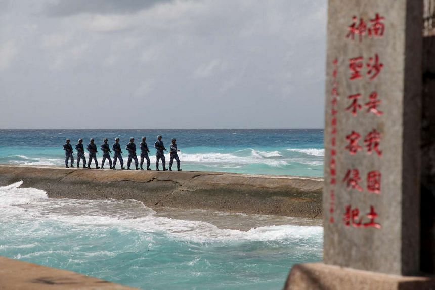 Soldiers of China's People's Liberation Army (PLA) Navy patrol near a sign in the Spratly Islands in the South China Sea.