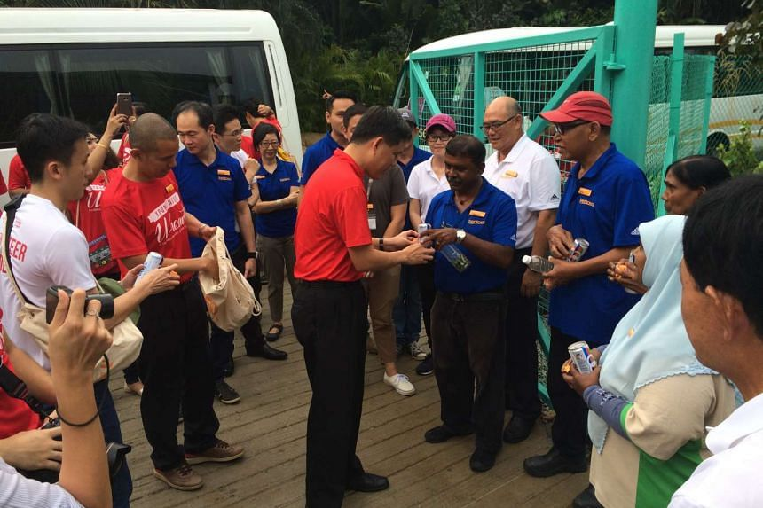 NTUC secretary-general Chan Chun Sing (centre) handing out gifts and drinks to workers at a plant nursery in Sentosa, during a surprise visit on July 13, 2016.