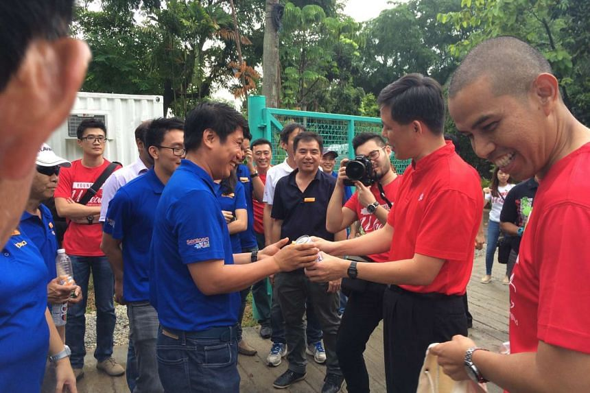 NTUC secretary-general Chan Chun Sing (right) handing out gifts and drinks to workers at a plant nursery in Sentosa, during a surprise visit on July 13, 2016.