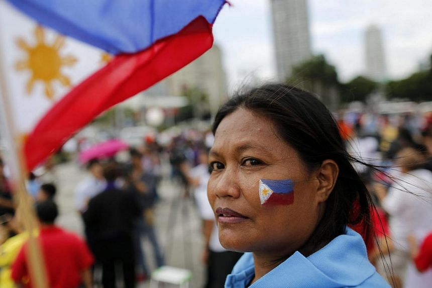 A Filipino with the Philippine national flag painted on her cheek looks on during a demonstration in Manila, Philippines.