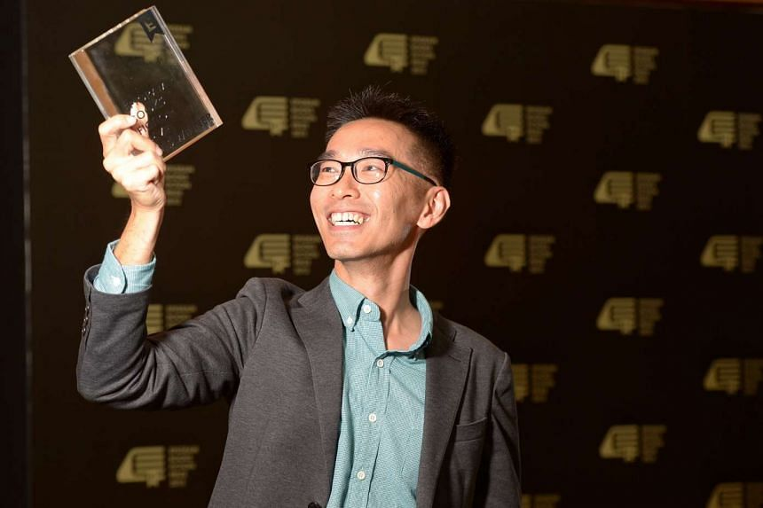 Writer O Thiam Chin holding up his trophy after winning the inaugural Epigram Books Fiction Prize, on Nov 5, 2015.