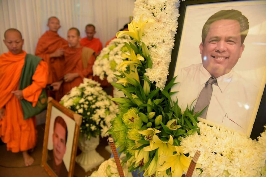 Cambodian Buddhist monks walk past portraits of Kem Ley during a funeral ceremony in Phnom Penh on July 12, 2016.