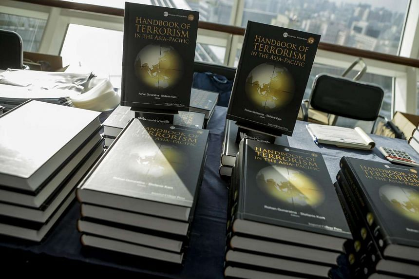 Stacks of books titled 'Handbook of Terrorism in the Asia-Pacific' are displayed on a table during the launch event of the book at the National Library on July 12 2016.