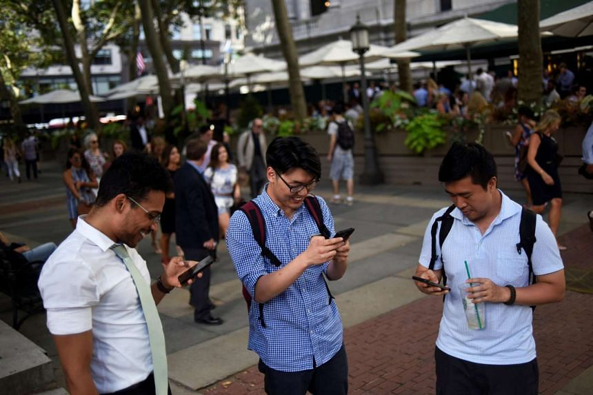 People play the augmented reality mobile game Pokemon Go in New York City.