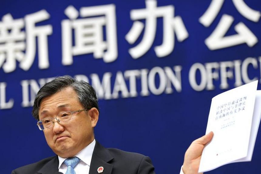 Chinese Vice Foreign Minister Liu Zhenmin holds up a policy paper on China's position on the ruling of an international tribunal on the South China Sea during a press conference in Beijing, China, 13 July 2016. China affirms its sovereignty over the