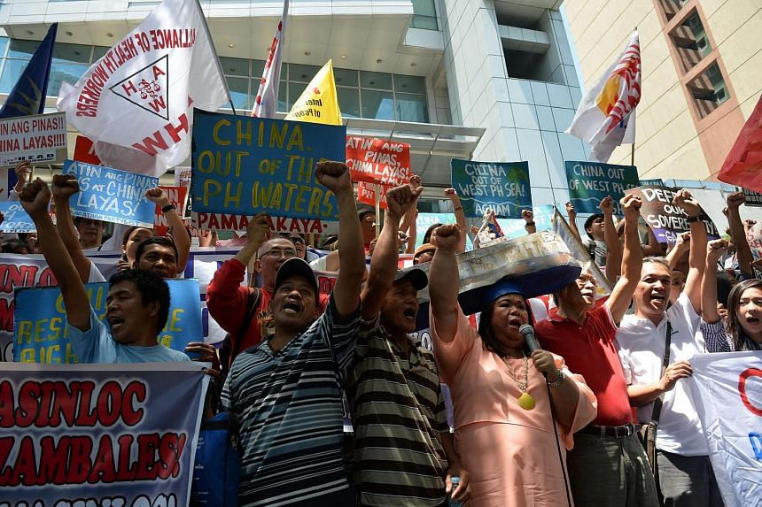 Activists hold placards during a protest in front of the Chinese consulate in Manila on July 12, 2016.