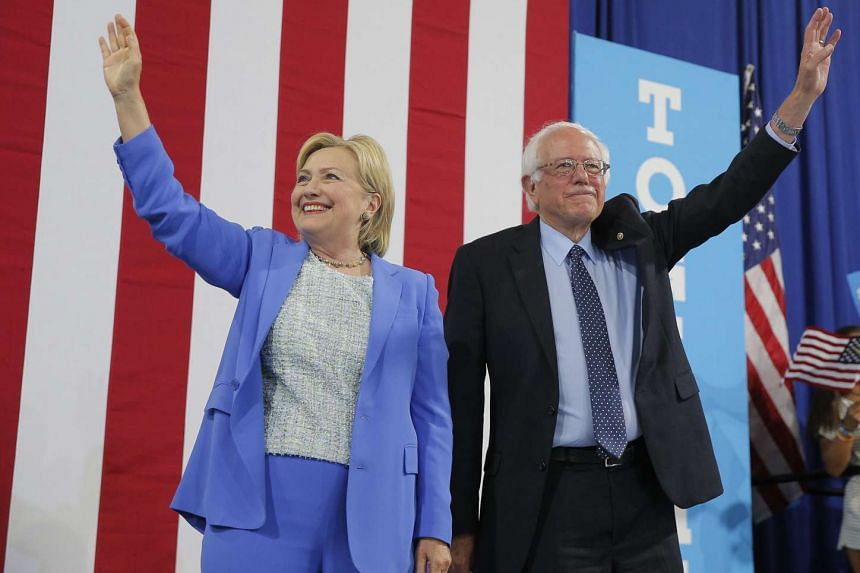 Hillary Clinton and Senator Bernie Sanders wave during a campaign event in Portsmouth, New Hampshire on Tuesday.