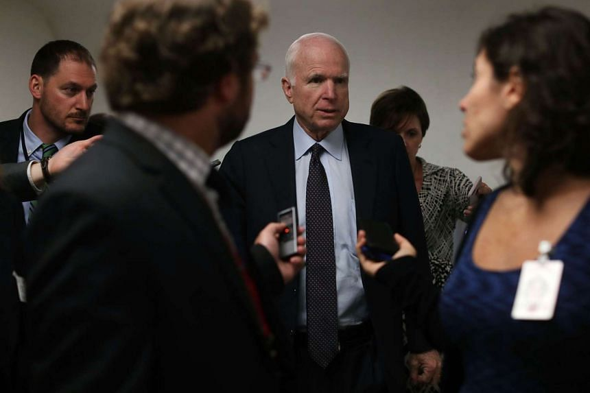 US Sen. John McCain centre is surrounded by the media as he arrives at the Capitol in Washington on Tuesday.