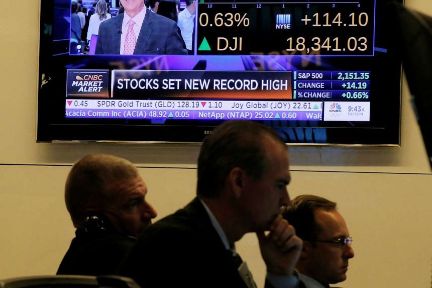 Traders work as the New York Stock Exchange (NYSE) hits new highs.