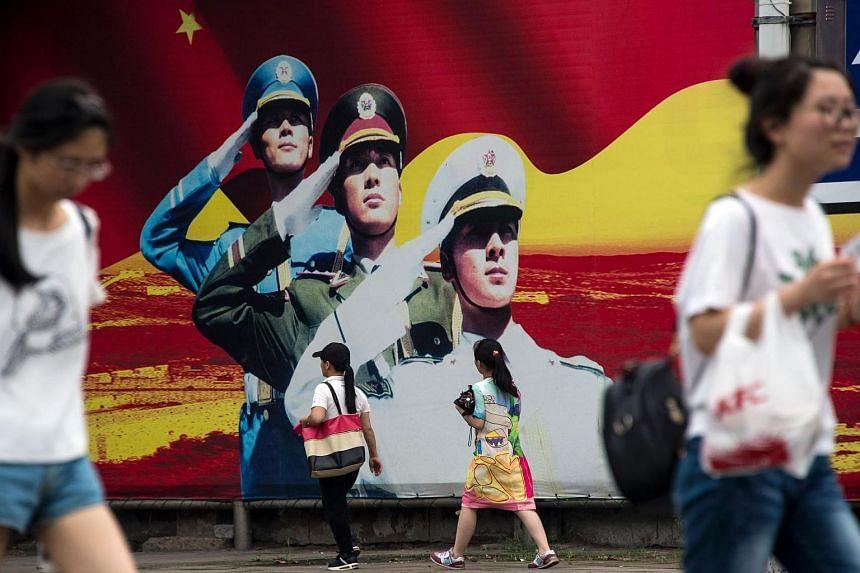 Pedestrians pass a military propaganda poster on a street in Shanghai.