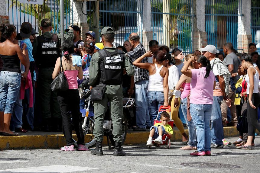 Venezuelan soldiers stand guard while people queue for cooking oil and margarine at a supermarket in Caracas on July 12, 2016.
