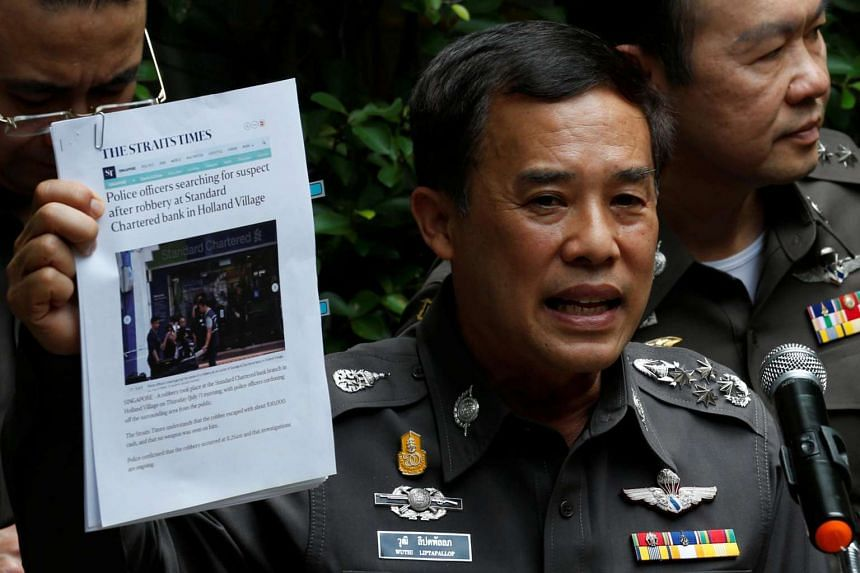 Thailand's deputy national police chief Wuthi Liptapallop holds up a printed copy of The Straits Times as he speaks during a news conference on the Standard Chartered bank robbery in Singapore.