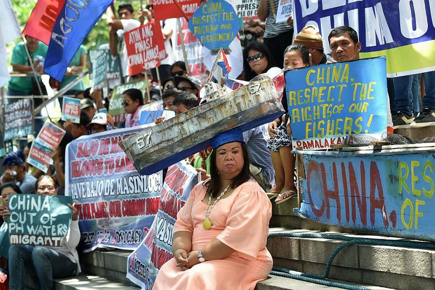 """An activist wearing a hat representing the Philippine navy boat """"Sierra Madre"""", now half-submerged at Second Thomas shoal of the Spratly islands, sits with protesters during a demonstration in front of the Chinese consulate in Manila on July 12, 2016"""