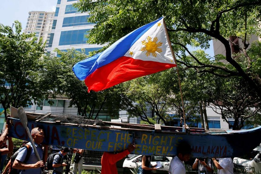 A Philippine national flag flutters on a part of a fishing boat with anti-China protest signs, as demonstrators march towards the Chinese Consulate, over the South China Sea disputes.
