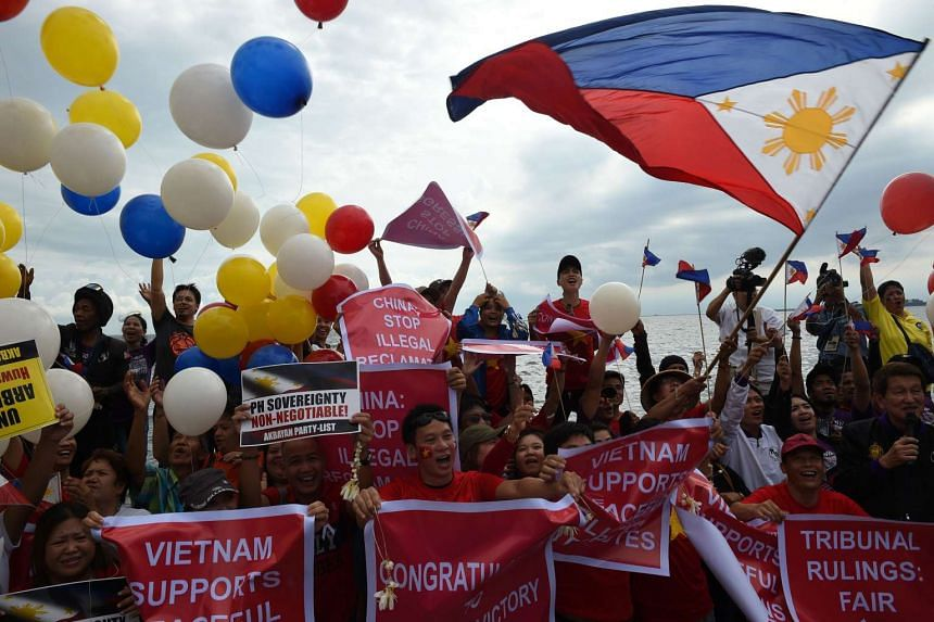 Filipino activists and Vietnamese nationals release balloons and wave Philippine flags during a demonstration along the bay walk in Roxas Boulevard in Manila on July 12, 2016.