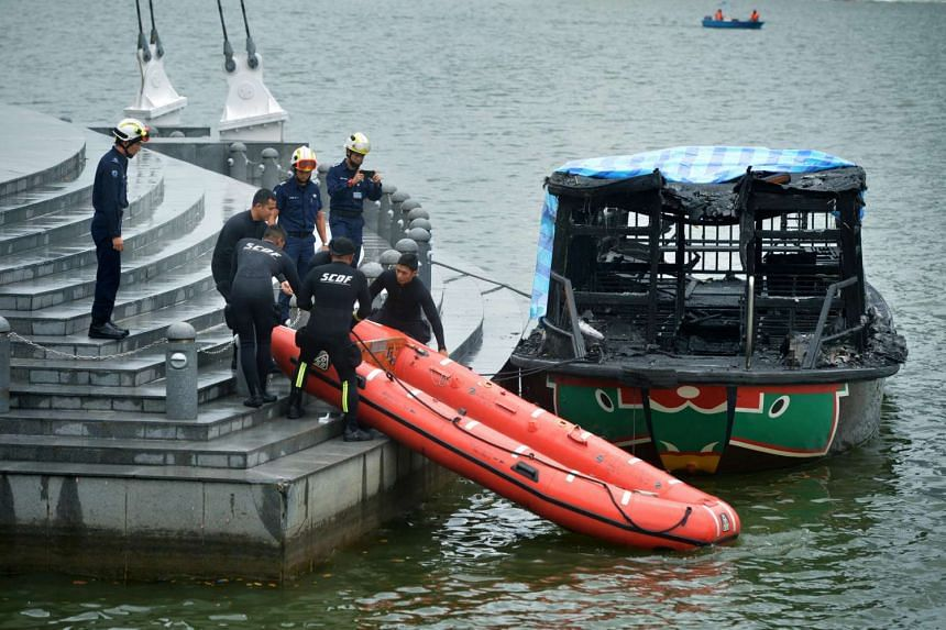 Members from the Singapore Civil Defence Force's diving unit prepare to launch their dinghy at the Esplanade's Outdoor Theatre to search for Mr Ong Hock Long.