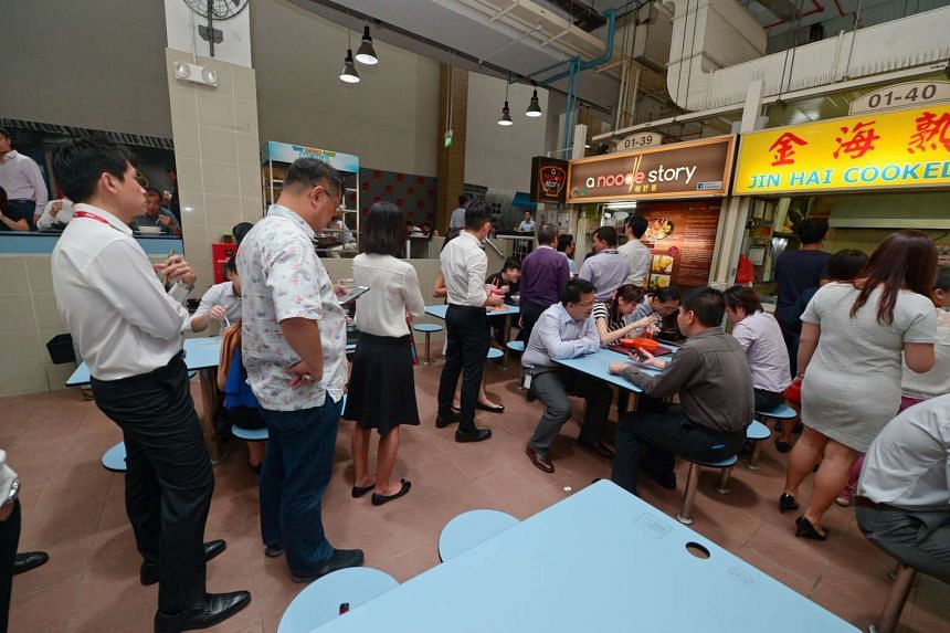 People queuing at hawker stall A Noodle Story during lunchtime at Amoy Street hawker centre.