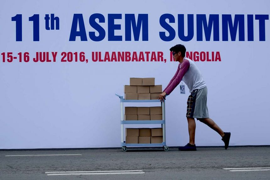 A man pushes a trolley past a poster of the 11th Asia-Europe Meeting (Asem) at Sukhbaatar Square in Ulaanbaatar, on July 14, 2016.