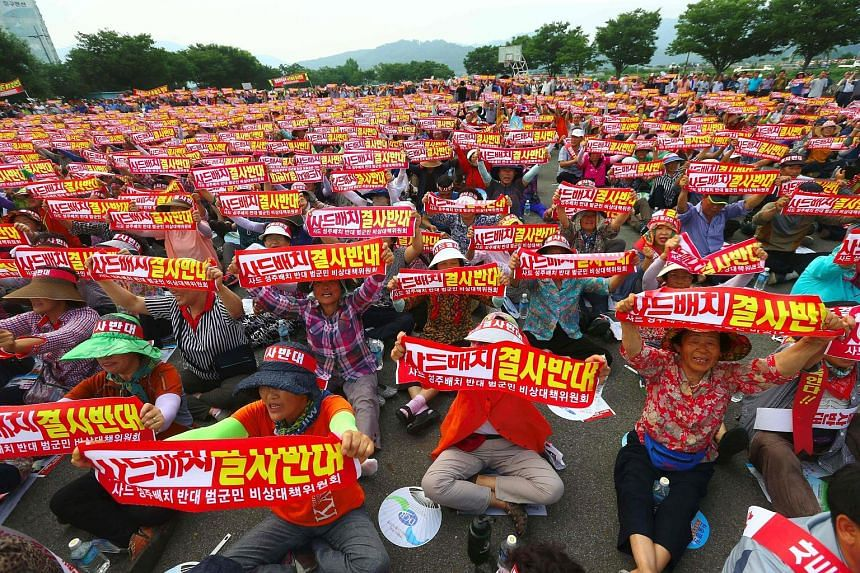 "Thousands of South Koreans holding up banners reading ""We absolutely oppose Thaad deployment"" during a rally yesterday against the planned deployment of the US-built Terminal High Altitude Area Defence system in Seongju. The system, meant to defend a"