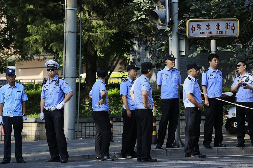Chinese police officers standing guard at a roadblock set up near the Philippine embassy in Beijing yesterday. Mr Liu with the White Paper on China's position on the ruling in Beijing yesterday. The minister said whether China needs an ADIZ in the So