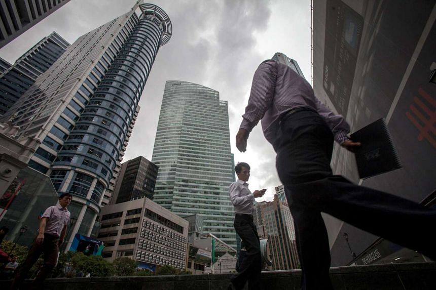 Pedestrians walk past office buildings in the central business district of Singapore in 2013.