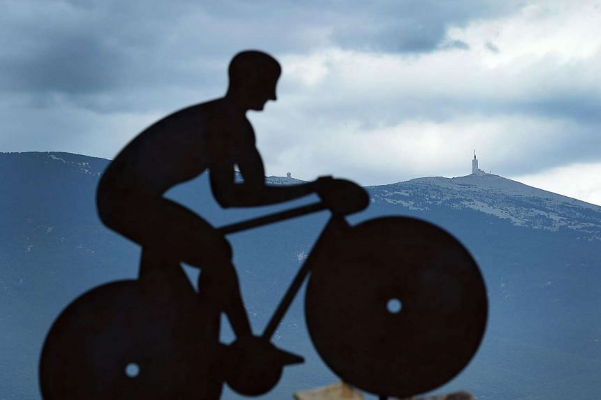 A picture taken on the Mont Ventoux on July 12, two days before the passage of the Tour de France shows a sculpture of a cyclist against the Mont Ventoux' summit.