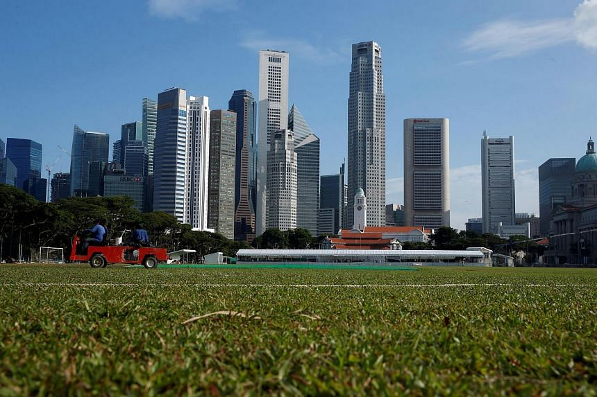 Workers tend to the pitch with the Singapore Central Business District skyline in the background on June 6.