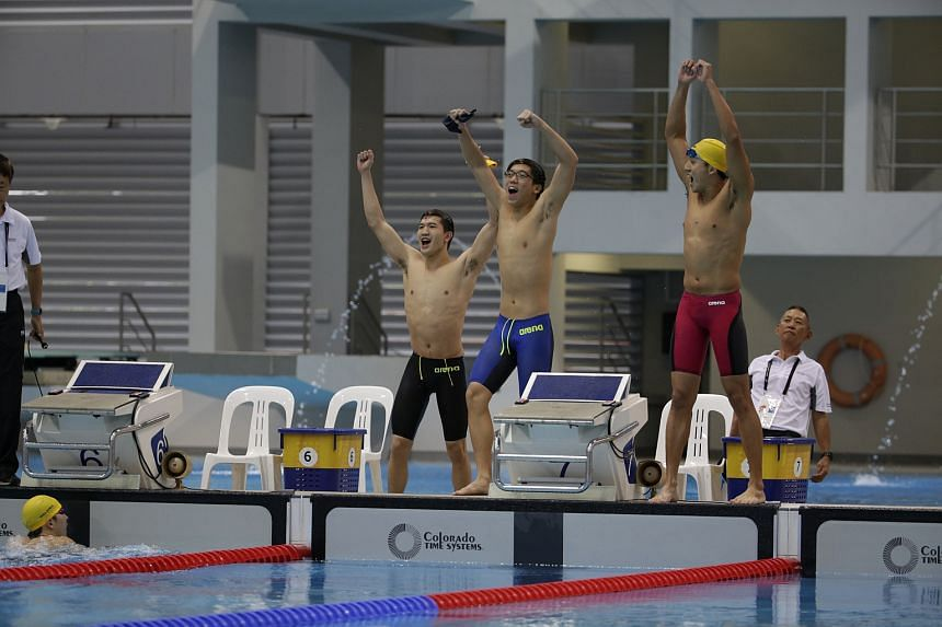 (From left) Malaysia's quartet of Foong Wei Tze (in water), Yeap Zheng Yang, Keith Lim and Kevin Yeap celebrate their men's 800m freestyle relay win in the swimming finals of the 18th ASEAN University Games at the OCBC Aquatic Centre on July 13, 2016