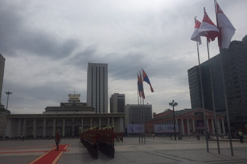 Honour guards stand at attention as the flags of Mongolia and Singapore flutter in the wind.