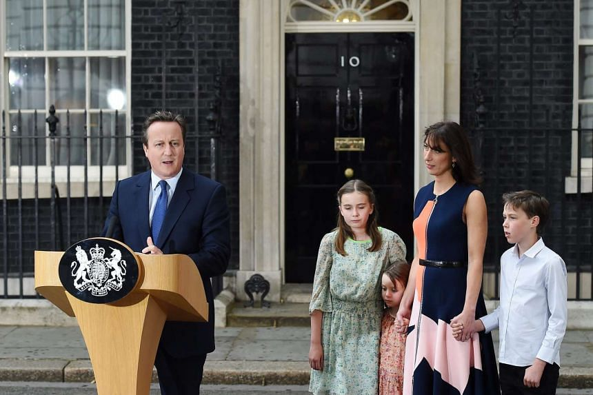 Outgoing British Prime Minister David Cameron (left) is accompanied by his wife Samantha and their children as he speaks on his final departure from No. 10 Downing Street.