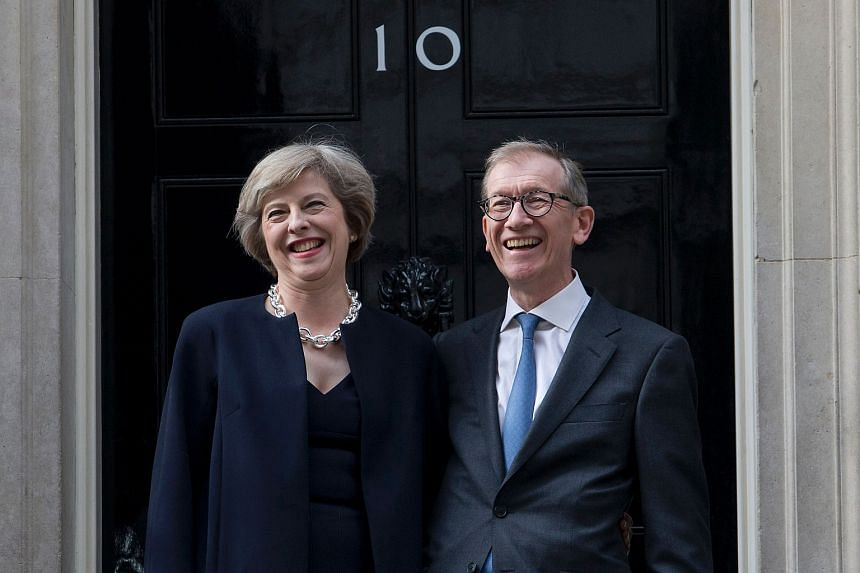 Britain's new Prime Minister Theresa May (left) and her husband Philip John May laugh together outside the door of 10 Downing Street in central London on July 13.