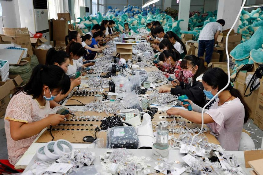 Workers in the process of making soft toys at a toy factory in Lianyungang, in eastern China's Jiangsu province, on July 12.