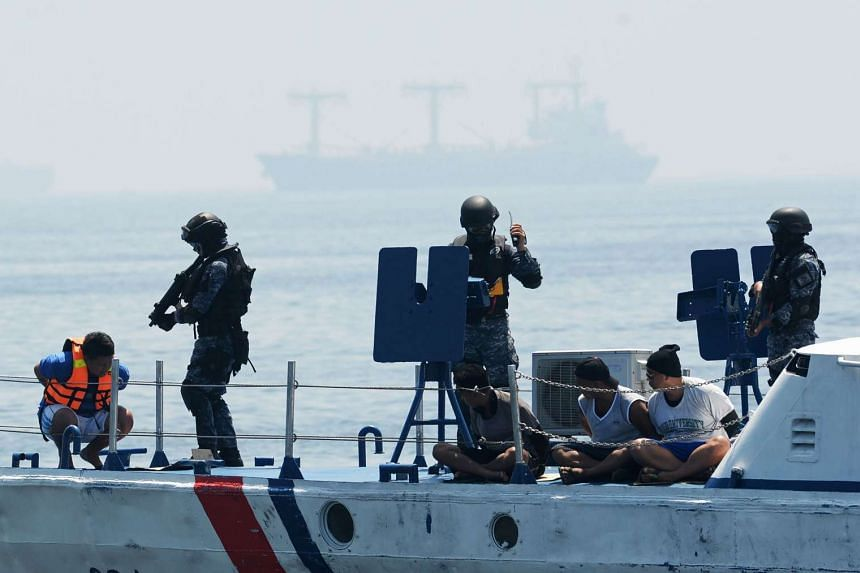 Philippine and Japanese Coast Guard personnel conduct a drill on board a Philippine Coast Guard boat at an annual anti-piracy exercise off Manila Bay on July 13, 2016.
