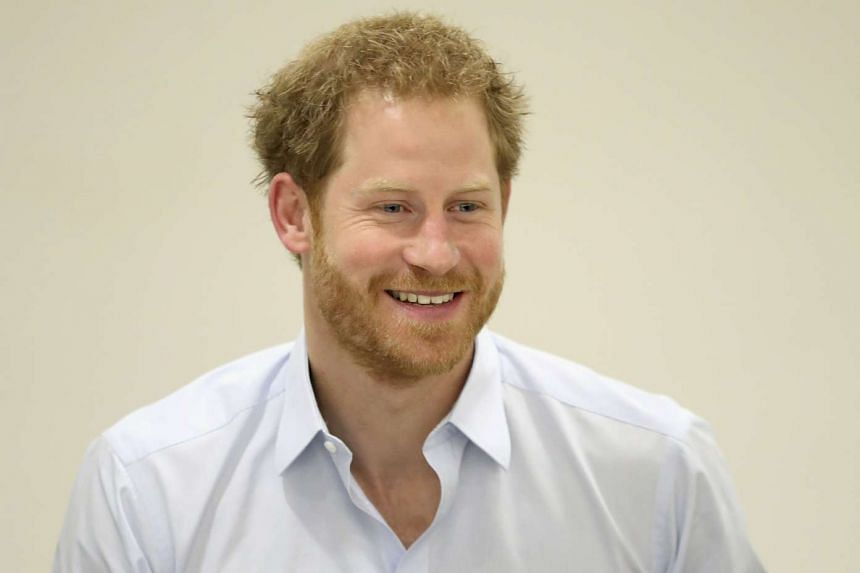 Prince Harry chats with staff during his visit to the Burrell Street Sexual Health Clinic in London, Britain, on July 14, 2016.