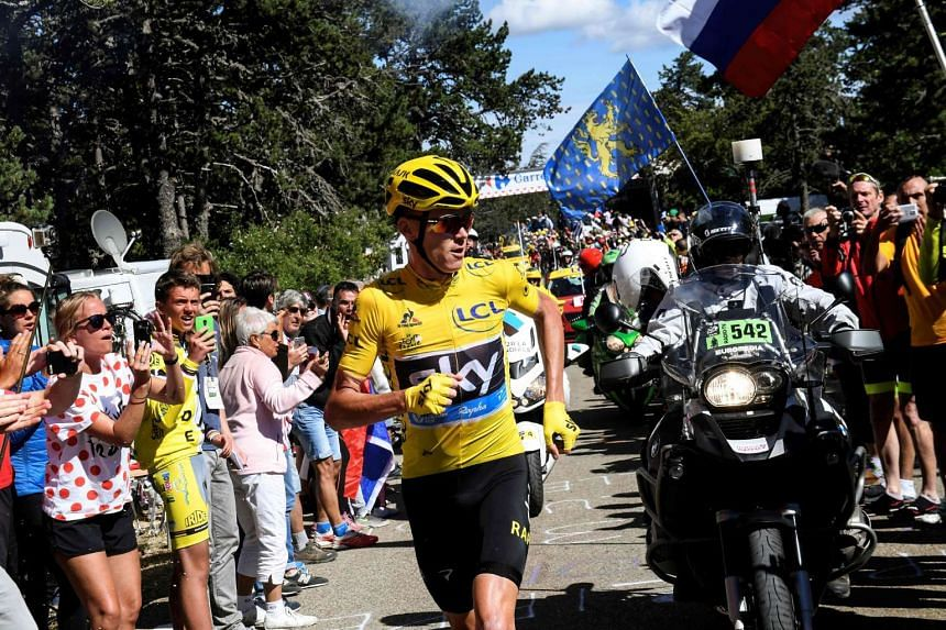 Froome (centre), wearing the overall leader's yellow jersey, runs to get a replacement bike.