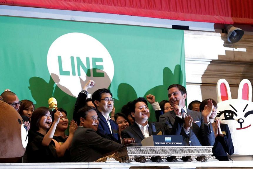 NYSE president Tom Farley (right) accompanies Japan's Line Corp CFO In Joon Hwang (second, left) and Chief Global Officer Jungho Shin (middle) and Chief Strategy and Marketing Officer Jun Masuda (second, right) as they ring the opening bell to celebr