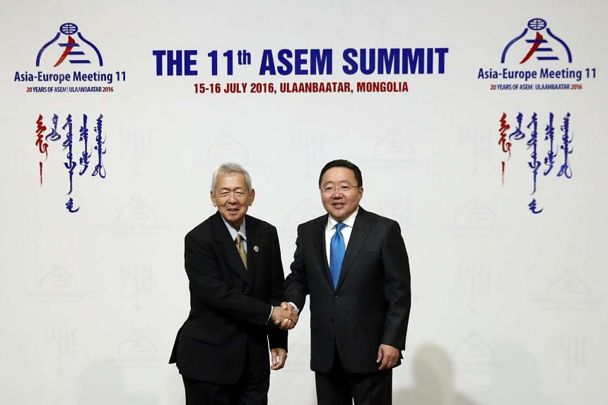 Philippine Foreign Affairs Secretary Perfecto Yasay (left) is greeted by Mongolia's President Tsakhiagiin Elbegdorj upon arrival for the opening of the 11th ASEM Summit in the Mongolian capital of Ulan Bator on July 15.