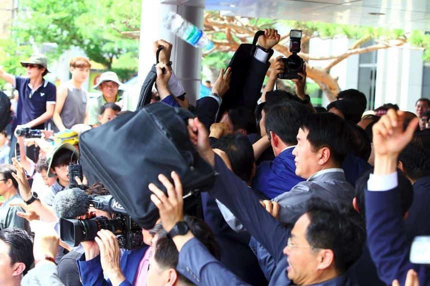 South Korean officials try to protect Prime Minister Hwang Kyo Ahn from water bottles and eggs being thrown by angry protesters, on July 15, 2016.