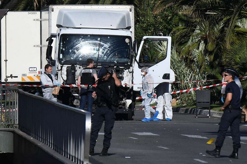 Forensics officers and policemen look for evidences in a truck on the Promenade des Anglais seafront in Nice on July 15, 2016.