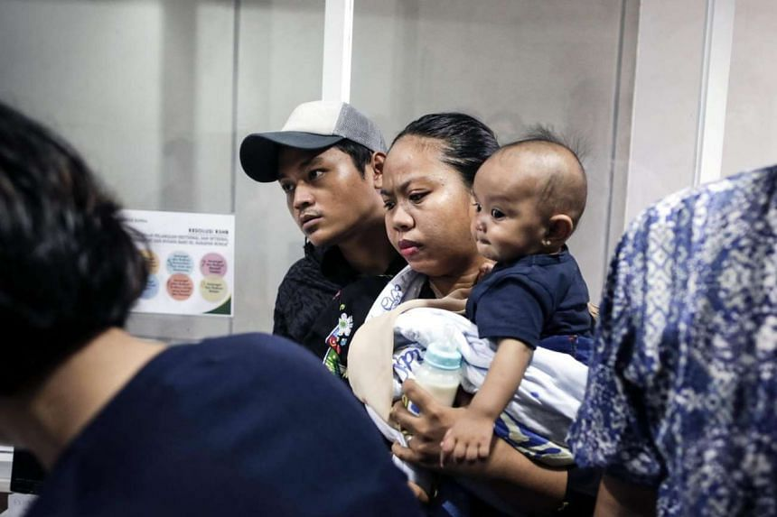 Indonesian parents gather as they check their kids' vaccination details during a protest against fake vaccines at Harapan Bunda hospital in Jakarta, on July 15, 2016.